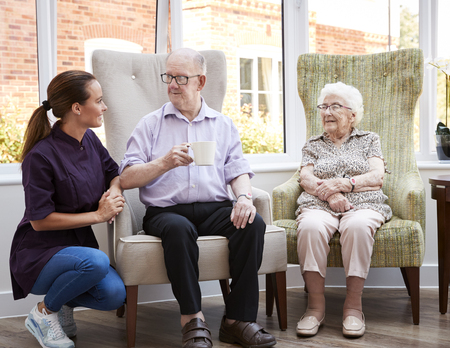 Male And Female Residents Sitting In Chair And Talking With Carer In Retirement Home Stock Photo