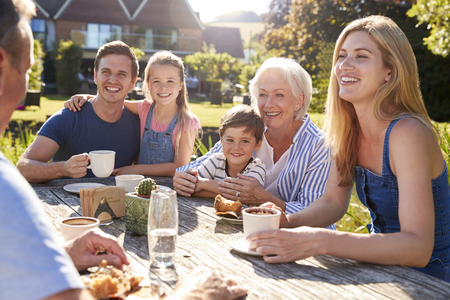 Multi Generation Family Sitting At Table Enjoying Outdoor Summer Drink At Cafe Stock Photo