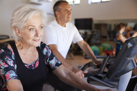 Active Senior Couple Exercising On Cycling Machines In Gym
