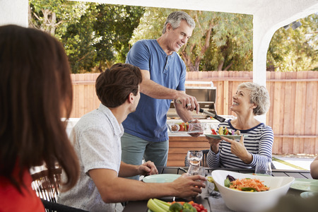 Senior dad serving his wife food at a family barbecue