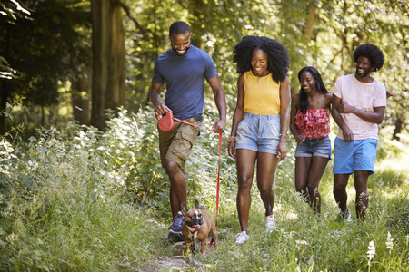 Two black couples walking with a dog in a forest Stock Photo