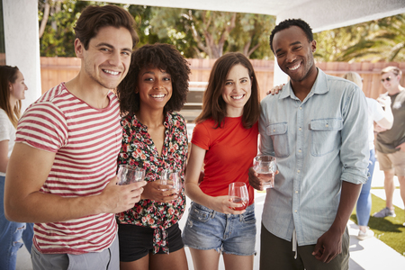 Young adult friends at a backyard party, looking to camera Stock Photo