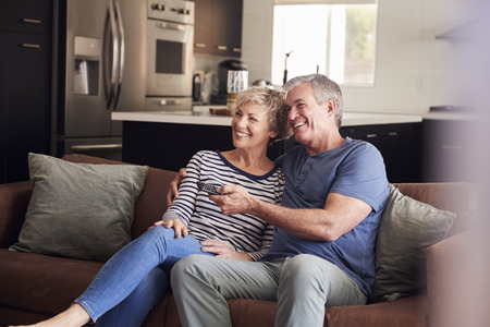 Senior white couple relaxing on couch watching television Stock Photo