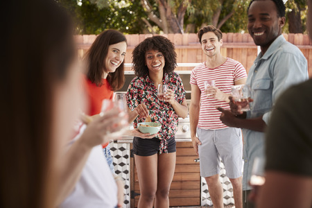 Young adult friends standing with drinks at a backyard party Stock Photo