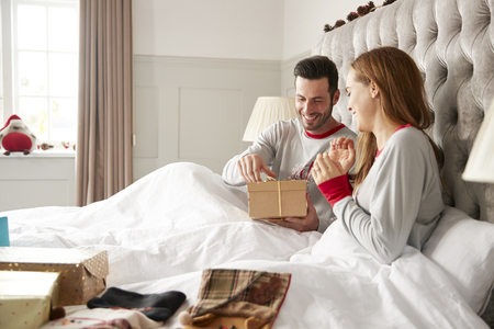 Excited Couple In Bed At Home Opening Gifts On Christmas Day Banco de Imagens