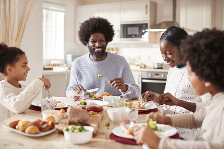Happy mixed race young family of four eating Sunday dinner together, front view