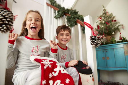 Portrait Of Two Excited Children Wearing Pajamas Sitting On Stairs Holding Stockings On Christmas Morning