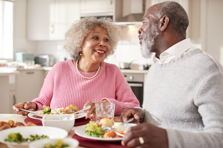 Senior black couple smiling to each other as they eat Sunday dinner together at home, close up Stock Photo - 111696582