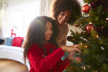 Madre e hija adornos colgantes en el árbol de Navidad en casa