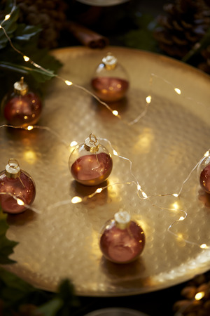 Close up of Christmas baubles on a gold table with warm glow, selective focus