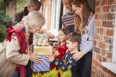Grandparents Being Greeted By Family As They Arrive For Visit On Christmas Day With Gifts Reklamní fotografie