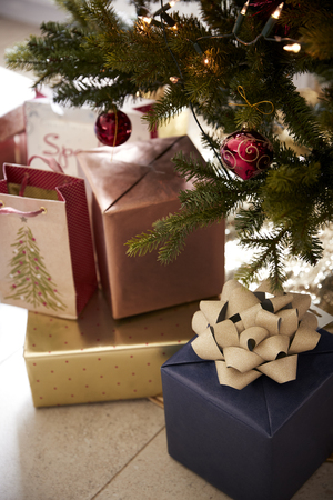 Gifts arranged under a decorated Christmas tree, close up Imagens