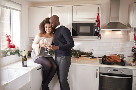 Young mixed race couple drinking champagne embrace in their kitchen while preparing Christmas dinner Banque d'images