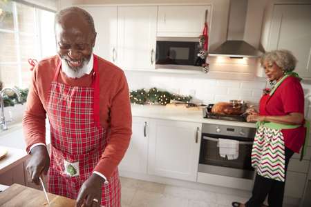 Mature black couple preparing Christmas dinner, man chopping vegetables in the foreground