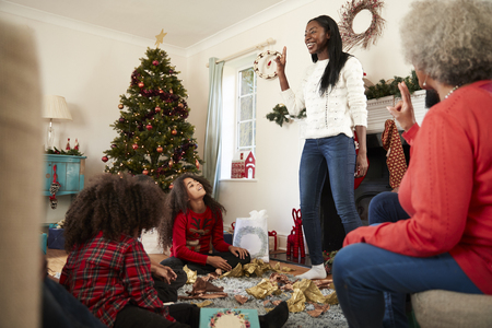 Multi Generation Family Playing Game Of Charades As They Celebrate Christmas At Home Together