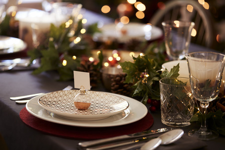 Christmas table setting with bauble name card holder arranged on a plate and green and red table decorations