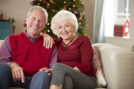 Portrait Of Senior Couple Sitting On Sofa In Lounge At Home On Christmas Day