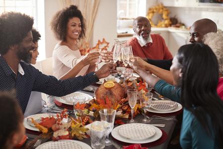 Familia de raza mixta de varias generaciones levanta sus copas para hacer un brindis en su mesa de la cena de Acción de Gracias
