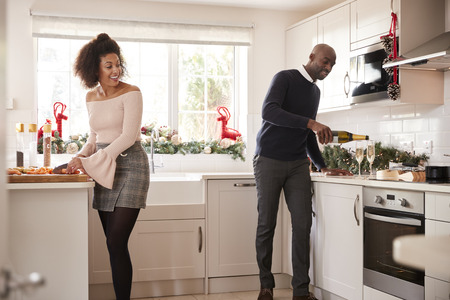 Young mixed race couple preparing Christmas dinner in the kitchen, the man pouring glasses of champagne Stock Photo