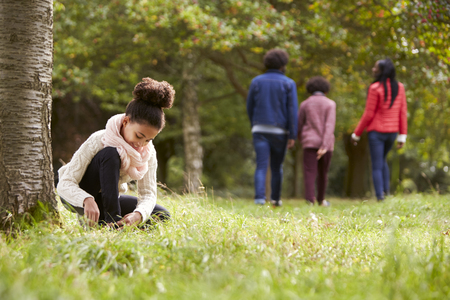 Mixed race girl kneeling in the park to tie her shoe, her family walking in the background, low angle Stock Photo
