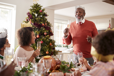 Black grandfather standing to make a speech and a toast at the head of the family Christmas dinner table, front view Stock Photo