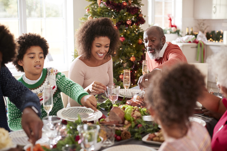 Young black woman eating Christmas dinner with her mixed race multi generation family, close up