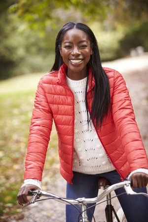 Young adult black woman sitting on a vintage bicycle in a park smiling to camera, front view, close up