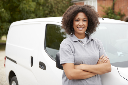 Young black female tradesperson standing next to her white van with arms crossed, close up Stock Photo
