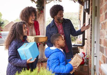 Family Standing At Front Door As They Arrive For Visit On Christmas Day With Gifts 스톡 콘텐츠 - 111696697