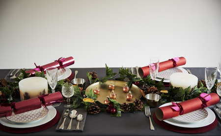 Decorated Christmas table set for four people, with Christmas crackers arranged on plates
