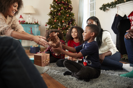 Son Giving Mother Gift As Multi Generation Family Celebrate Christmas At Home Together