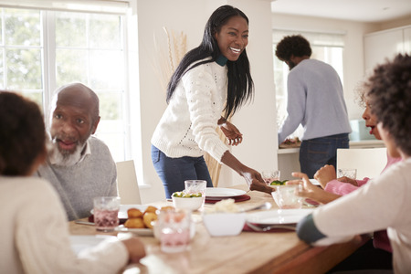 Black couple bringing food to the table for Sunday family dinner for the kids and grandparents