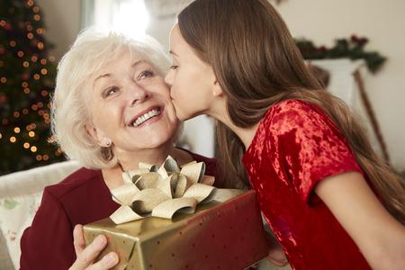 Abuela recibe un regalo de Navidad de su nieta en casa