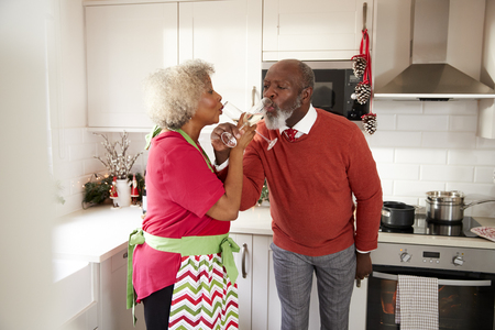 Mature black couple celebrating on Christmas day drinking a toast with arms entwined, selective focus