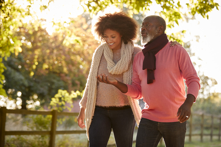 Senior Father With Adult Daughter Enjoying Autumn Walk In Countryside Together Stock Photo