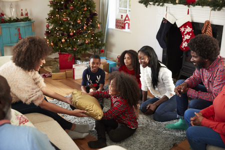 Mother Giving Daughter Gift As Multi Generation Family Celebrate Christmas At Home Together