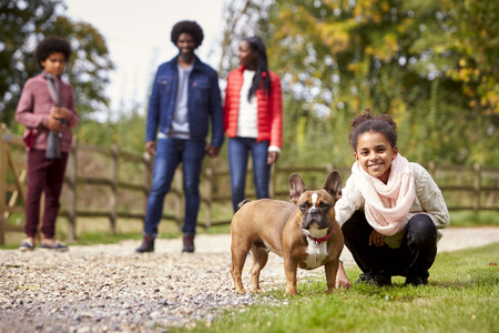 Mixed race girl squatting to pet her dog during a family walk in the countryside looking to camera, low angle