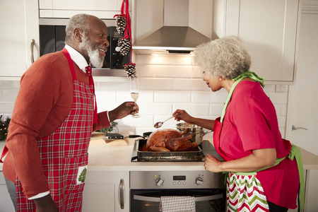 Mature black couple preparing Christmas dinner in their kitchen, man raising a glass as his wife bastes the roast turkey Banco de Imagens