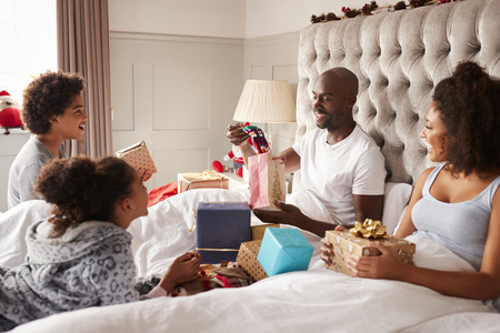 Mixed race family watching dad opening a gift in bed on Christmas morning, close up