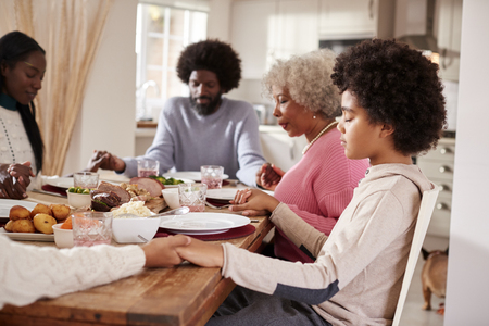 Multi generation mixed race family holding hands and saying grace before eating their Sunday dinner, side view
