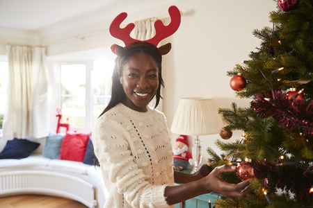 Portrait Of Woman Wearing Antlers Hanging Decorations On Christmas Tree At Home Stock Photo