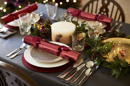 Close up of Christmas table setting with Christmas crackers arranged on plates and red and green table decorations, elevated view