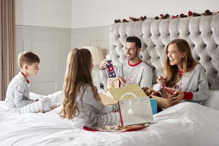 Parents Opening Gifts From Children As They Sit On Bed Exchanging Present On Christmas Day Stock Photo