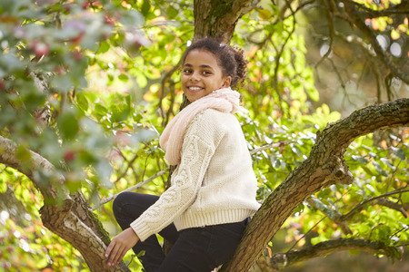 Young girl sitting in an Autumn tree, turning and smiling to camera, side view Stock Photo