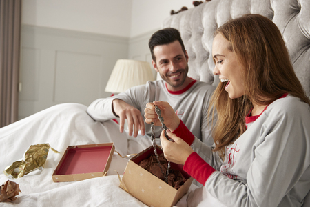 Woman Opening Gift Of Necklace In Bed At Home As Couple Exchange Presents On Christmas Day