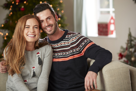 Portrait Of Couple Wearing Festive Jumpers Sitting On Sofa In Lounge At Home On Christmas Day
