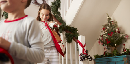 Two Excited Children Wearing Pajamas Running Down Stairs Holding Stockings On Christmas Morning