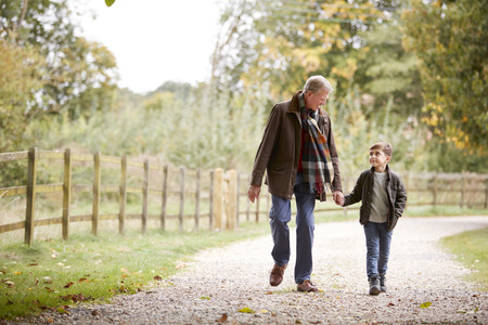 Grandfather With Grandson On Autumn Walk In Countryside Together Stock Photo