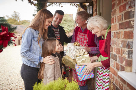 Family Being Greeted By Grandparents As They Arrive For Visit On Christmas Day With Gifts Reklamní fotografie