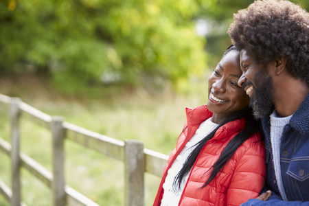 Black adult woman leaning on the shoulder of her boyfriend, standing in the countryside, close up Stock Photo